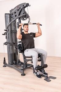 Beim Latziehen an einer Kraftstation trainieren Sie effektiv Rücken und Schultermuskulatur
